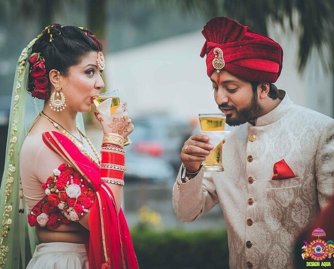 A beautiful candid picture where the bride and the groom commit to each other to share love till the end and enjoying a sip of drink in occassion of their wedding.