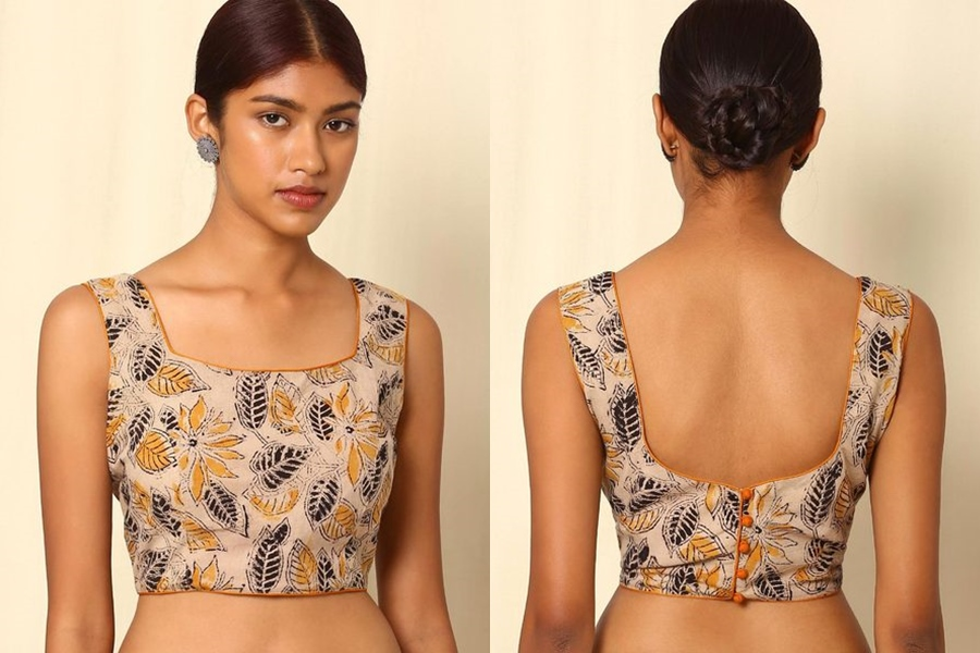 This is a simple kalamkari print cotton blouse marked by little buttons at the back which successfully attempts to give it a new shot. If you are a person who loves wearing saris Everytime then you should definitely have this one.