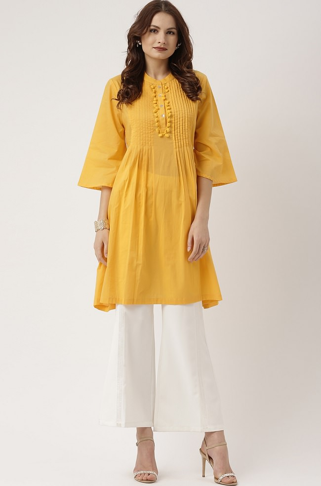 This kurti is very popular and caried by not only youngters but also women. this kurti reaches till calf & is known as A-line kurti because of the flare that starts from waist giving it a shape. A simple stand collar yeelow A-Line kurti paired with white plazzzos with little detailing is looking so chic to be carried to any simple events.