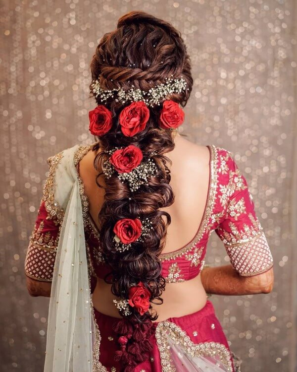 Beads and red roses on the messy curls and braids.